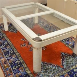 Circa 1980 Glass Top Coffee Table with Leaves: A circa 1980 glass top coffee table with leaves. This rectangular top features two glass inserts to the top, along with two additional wooden leaves. Silver-toned triangular metal accents are to each corner. The wood is finished in an off-white color with a wavy pattern. The table rises on four triangular shaped legs with curved outer edges, ending in silver-toned caps.