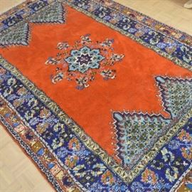 """Hand-Knotted Moroccan """"Rabat"""" Area Rug: A hand-knotted Moroccan """"Rabat"""" area rug. The rug features a central eight-pointed star medallion in light blue, dark blue, black, and cream on a deep orange field. The field offers triangular guls along each end in a complementary color palette and is enclosed by a compound border. The border features a floral pattern in dark and light blue with orange accents throughout. It has fringe to either end and is tagged to the back """"Morocco, Rabat""""."""