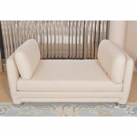 Off-White Padded Upholstered Daybed: An off-white padded upholstered daybed. This vintage circa 1980 daybed is backless, with square arms, each with a cushion. It stands on upholstered legs ending in silver-toned round cap feet. For coordinating pieces, see items 17CHI132-010 and 17CHI132-011.