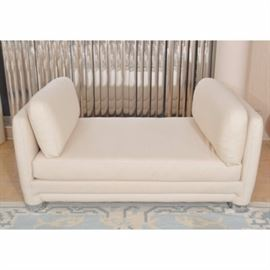 Off-White Padded Upholstered Daybed: An off-white padded upholstered daybed. This vintage circa 1980 daybed is backless, with square arms, each with a cushion. It stands on upholstered legs ending in silver-toned round cap feet. For coordinating pieces, see items 17CHI132-009 and 17CHI132-010.