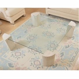 Modern Style Floating Glass Panel Coffee Table: A Modern style coffee table. This table features a floating glass panel design with a squared panel set into the edge of four quarter-round supports. The supports have a textured cream and taupe design and the piece is unmarked.
