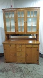 1923 Stepback Cupboard. Tigerwood Oak. Made local in Wirtz VA.  Very solid,very heavy. Has glass front cabinets on top and beveled mirror in center.  One solid piece.