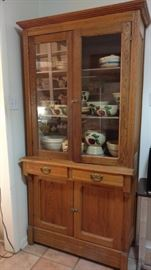antique oak storage cabinet in laundry room