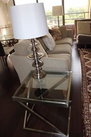 One of two matching glass and chrome end tables and one of two matching table lamps.