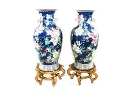 Pair of Large Chinese Vases: A pair of large matching Chinese vases. These decor pieces have an all-over floral and foliate design, in hues of blue, pink, green and yellow. Both come with wooden bases.