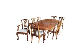 Federal Style Mahogany Dining Table: A federal style mahogany dining table, with two inserted leaves, and tapered reeded legs. This table has been paired with eight Chippendale style dining chairs, two captain style and six guest, boasting of open-work backs with ornate floral and foliate accents.