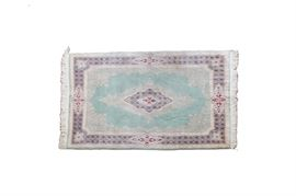 Persian Style Accent Rug: A Persian style wool accent rug. This piece has an all-over floral and foliate pattern, set upon a mint green background with a central diamond shaped medallion and border with crimson, blue, cream, and beige accents. Both edges have fringe.