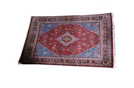 Large Persian Rug: A large Persian rug with an all-over floral and foliate design on a crimson background; further accented in hues of blue, green, beige, cream and brown.