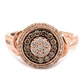 Sterling Silver Rose Gold Wash Diamond Ring: A sterling silver rose gold wash diamond ring. The ring has a cluster of diamonds to center with double brown and white diamond halos, having baguette accents to the shoulder.