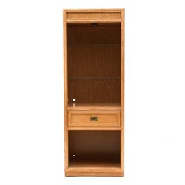 Stanley Oak Cabinet: A tall oak cabinet by Stanley Furniture. Some parts are solid oak and some are veneer. It has three adjustable/removable glass shelves to the main cabinet space. There is a light mounted to the top, with a dimmer switch, which was tested and working at the time of cataloging. Below the main cabinet space is a single drawer, above an open lower shelf. See also 17CIN466-213, a similar but not identical cabinet by Stanley.