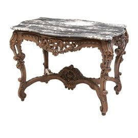 Stone Top Table with Carved Base: A dining table with a gray marble top and a carved hardwood base. The top has a wavy shaped edge but is approximately rectangular. The base has S-curved legs joined by spreaders and is densely carved with floral and foliate designs. Unmarked.