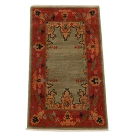 Tufenkian Hand Knotted Tibetan Wool Accent Rug: A hand knotted Tibetan wool accent rug by Tufenkian Carpets. This traditional Setana rug features a variegated muted olive center ground with accent designs in brown, black and red, having a ruby red guard border with stylized palmettes and lancet leaf forms. The rug is finished with overcast selvage edges and short warp fringe to opposite ends. Tufenkian rugs are made of unbleached wool which has been hand carded, spun and dyed by hand. Made in Nepal with makers labels to the verso.