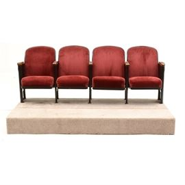 Set of Theater Seats: A set of four theater seats, attached as one piece. They have black metal frames, burgundy corduroy-texture fabric upholstered seats and backs, and oak armrests. The seats can fold. Includes two platforms, each with a pine frame covered in beige carpeting, with plastic disc feet to the underside. See also 17CIN466-270 and -271.