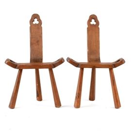 Pair of Vintage Birthing Chairs: A pair of vintage birthing chairs. The hardwood chairs have a walnut finish, a curved seat, and narrow back. The seats and back have an openwork trefoil design. Raised on three legs that are squared and flared. Unmarked.