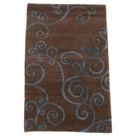 Hand Knotted Tibetan Wool Accent Rug by Tufenkian Carpets: A hand knotted Tibetan wool accent rug by Tufenkian Carpets. This artisan rug features an asymmetrical swirling blue design on a chocolate brown field. The rug is finished with overcast selvage edges and turned under ends. Tufenkian rugs are made of unbleached wool which has been carded, spun and dyed by hand. Made in Nepal with makers labels to the verso.