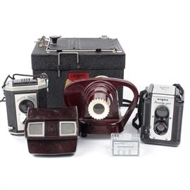 Vintage Cameras and Accessories: A collection of vintage cameras and accessories including an Eastman Kodak Brownie Reflex in box, a 3-D View Master in original box, a View Master Junior projector, an Argus Arogflex in leather holder, housed in original box with instructions, and a Vintage Jackson 35 mm printer.