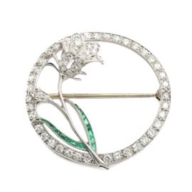 Platinum and 18K White Gold Emerald and 1.03 CTW Diamond Floral Brooch: A platinum and 18K white gold emerald and 1.03 ctw diamond floral brooch. This brooch features an open diamond encrusted circular body housing a single stem flower with channel set emerald leaves beneath a diamond set flower.