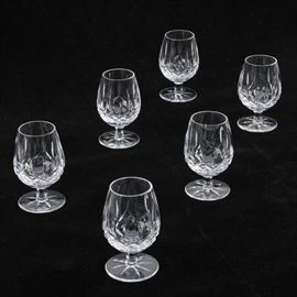 Set of Six Waterford Crystal 'Lismore' Snifters: A set of six Waterford Crystal Brandy glasses. This set of fine crystal snifters have a wide crystal bowl with diamond crosshatch cut detailing on the exterior of the glass. The goblets are held up by an edged stem leading to a round base with a cut starburst pattern. Each glass has been acid marked with the iconic Waterford brand logo on the underside of the base.