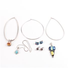 "Sterling Silver Jewelry With Gemstones and Dichroic Glass: A collection of sterling silver jewelry including a Carolyn Pollack Relios faux turquoise enhancer pendant with snake chain marked with a Relios ""R"" and crescent hallmark, ""925 ©""; an orange glass pendant with omega chain marked ""925 Italy""; two omega chains, both marked""925 Italy""; a dichroic Glass and smoky quartz pendant marked ""925""; Liz Palacios Enameled base metal flowers earrings with sterling lever back closures and Swarovski crystal centers, marked ""Liz Palacios""; and a pair of Nicky Butler Earrings with enamel inlay, marked ""NB 925 Sterling"". ""Each piece is tested or hallmarked as sterling silver and the total weight inclusive of all materials is 3.905 ozt."""