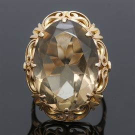 14K Yellow Gold Citrine 24.29 CT Ring: A 14K yellow gold and citrine 24.29 ct ring. This statement ring features an oval faceted prong set citrine in a decorative filigree setting.