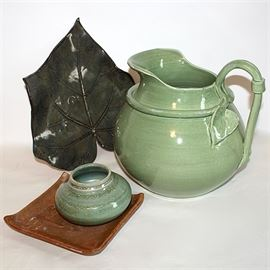 "Artisan Pottery Group Includes Arhaus Italian Made Pitcher: An artisan pottery group includes Italian made pitcher in soft green glaze with a sculpted leaf and vine handle and wide pour spout. The four piece group also include a large sculpted leaf shape platter after the large leaves of the sycamore tree, a small square plate with upcurled corners and an embossed dragonfly set to the upper left corner, and a small green glazed bowl with narrow neck. PItcher is stamped to the bottom ""Made in Italy for Arhaus"" and the other three pieces are marked to the verso with the artisan signatures."