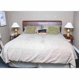 King Leather Bed: A king sized bed with brown leather upholstered headboard. Bedding included.