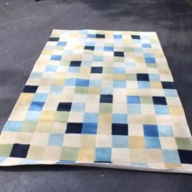 Back Porch Area Rug: A Back Porch rug. Power loomed wool rug features repeating pattern of blue color block on a cream ground. Maker's tag to reverse.