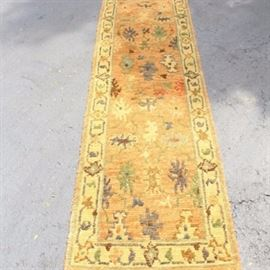 Hand-Knotted Indo-Persian Carpet Runner: A hand-knotted wool carpet runner. This rug features a thick wool pile in tones of gold. Stylized flowers fill an ocher field in hues of brown, yellow, green and orange, surrounded by an abstract border on a gold ground. It has overcast edges on all sides and is unlabeled.