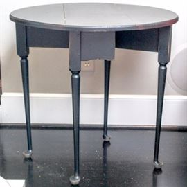 Vintage Drop Leaf Gateleg Table: A vintage drop leaf gateleg table. This wooden side table in black distress finish features drop leaves and swing out supports and legs. Unmarked by maker.