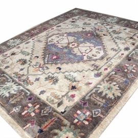 "Tahoe Hand-Knotted ""Heriz"" Wool Area Rug: A hand-knotted wool area rug in the Heriz pattern by Tahoe. In a muted palette of blue, burgundy, cream and greens, this wool rug is hand knotted with New Zealand wool and has maker's label to reverse. Made in India."