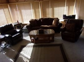 Living room sofa/couch, 3 recliners (2 show slight wear) Glass top coffee table, area rug, stereo. (wood chip burning heater not for sale)