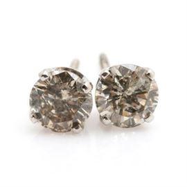 14K White Gold 0.83 CTW Diamond Stud Earrings: A pair of 14K white gold diamond stud earrings. Each earring has a four prong setting housing a round brilliant cut diamond.