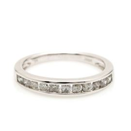 10K White Gold Diamond Channel Ring: A 10K white gold diamond channel ring. This ring features a channel of tension set diamonds to the crown of a polished white gold band.
