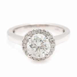 14K White Gold 1.97 CTW Diamond Ring: A 14K white gold 1.97 ctw diamond ring. This ring features a 1.72 ct round brilliant cut diamond prong set above a halo of round brilliant cut diamonds. The ring features an open gallery with scroll motif leading to a highly polished shank.