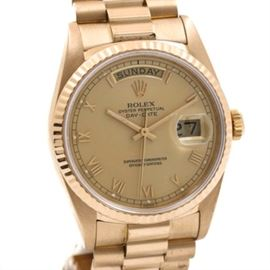 """Rolex Oyster Perpetual Day-Date 18K Yellow Gold Wristwatch: A Rolex Oyster Perpetual Day-Date 18K yellow gold wristwatch. This watch features a gold president band leading to a circular case housing a gold dial with gold tone slender hands, gold tone dash and Roman numeral hour indicators, two calendar sub-dials, and imprinted with """"Rolex Oyster Perpetual Day-Date Superlative Chronometer Officially Certified."""""""