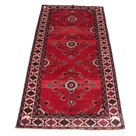 Hand-Knotted Signed Persian Heriz Area Rug: A hand-knotted signed Persian Heriz area rug. The scarlet colored field displays three cruciform medallions with floral accents throughout. A hand knotted signature is present at the lower portion of the field. A repeating minor gul and bar border surrounds the field. Cotton warp fringe is present at either end of the rug. Unmarked.