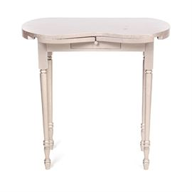 Vanity Table with Extendable Armrests: A vanity table with extendable armrests. This piece features a silver-tone painted exterior, extendable arms that follow shape of curved front when closed, and a drawer centered in front with a wooden pull atop turned legs.