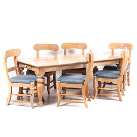 Rustic Dining Table and Chairs: A rustic dining table and chairs. The elongated oak table with pickled finish features four bulbous turned legs and rounded corners. There is a drawer at each end of the table with round wooden pull. The table is accompanied by six dining chairs. The chairs features blue upholstered seats.