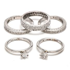 Sterling and Cubic Zirconia Rings: A selection of five sterling silver rings set with cubic zirconia. The rings have a variety of styles, including a solitaire stone in the shape of a heart, channel-set and pavé designs. The total weight, inclusive of all materials, is 0.375 ozt.