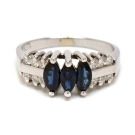 14K White Gold Sapphire and Diamond Ring: A 14K white gold sapphire and diamond ring. This white gold ring features three faceted marquise cut blue sapphires along with six round brilliant cut diamonds to each shoulder.