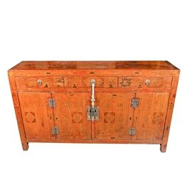 Vintage Asian Themed Credenza: A vintage Asian themed credenza. This wooden piece has a tassel and brass hardware. The top of the chest has three drawers with two hinged doors underneath. It is perched on four short tapered legs and features patterned gold etchings throughout. The piece does not bear any visible maker's marks.