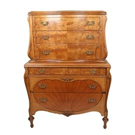 Antique Louis XVI Style Bombe Form Chest on Chest: An antique Louis XVI style bombe form chest on chest. The piece features figured and bookmatched veneers including fiddleback and birdseye maple and applied carvings. Scrolled stiles and curved sides lend the bombe form to this piece. The piece has a two part design of three stacked drawers over decorative waist molding and a lower chest with graduated drawers. Both pieces include decorative brass pulls and rise up on turned and fluted trumpet feet.