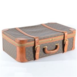 """Vintage Louis Vuitton Suitcase: A vintage Louis Vuitton suitcase. This classic rectangular piece of luggage features the iconic monogram print coated canvas construction with brown leather trim and gold tone hardware. It offers a zipper closure, buckled leather straps and a hinged leather handle. The interior is fully lined. Made under license by The French Company. A tag to the inside reads """"Made in France for Saks Fifth Avenue"""". Comes with a luggage tag and the original paper tag from Louis Vuitton in Paris, France."""