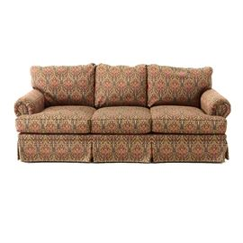 """Contemporary Rolled Arm Sofa By Fairfield: A contemporary sofa by Fairfield. The sofa features a low straight back with rolled arms, having three loose seat and back cushions, on a fully skirted base. The sofa is upholstered in a jewel tone woven jacquard paisley pattern fabric against a dark ground, with welted trim. Marked with an affixed """"Fairfield"""" label to the base. For a companion sofa, see item: 17CIN487-064"""