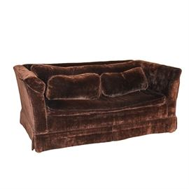 Brown Micro Velvet Loveseat: A brown micro velvet loveseat. This piece features a box design with straight crest back and sides at even height, surrounding rectangular cushion back and seat. The piece includes bolster pillows and a pleated skirt. It is upholstered in a brown micro velvet fabric and coordinates with item 17ATL101-501.