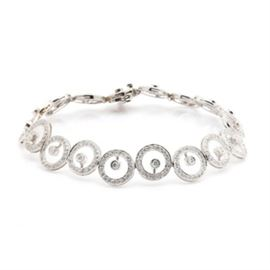 18K White Gold 2.25 CTW Diamond Bracelet: An 18K white gold 2.25 ctw diamond bracelet. This bracelet showcases three hundred and seventy-eight round brilliant cut diamonds adorned throughout the concentric design. This piece features a decorative hidden box tab clasp with a safety catch.