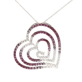 18K White Gold Pink Sapphire, Ruby and Diamond Pendant With 14K White Gold Chain: An 18K white gold pink sapphire, ruby and 0.97 ctw diamond pendant with a 14K white gold chain necklace. This pendant features an openwork heart motif, which graduates down in size to the center and steps down in depth. The gemstones also graduate in color from diamonds to variegated colors of pink sapphires and rubies. A 14K white gold chain necklace is included.