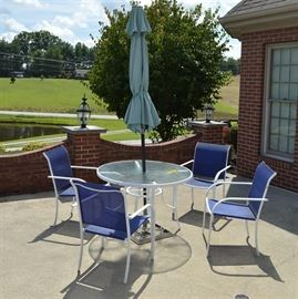 Patio Table with Umbrella and Four Chairs: A patio table with umbrella and four chairs. This includes one metal-framed table with a circular, hammered glass top; it rests on four splayed legs and its frame is painted white. The included umbrella has a light green shade and black pole. Each armchair features a white metal frame with a blue fabric seat and back.