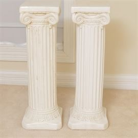 Pair of White Neoclassical Ceramic Columns: A pair of white Neoclassical ceramic columns. This pair of matching white ceramic Neoclassical columns features flat square tops, scrolling aprons, ridged columnar pedestals and square bases.