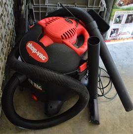 "Shop Vac Wet and Dry Vacuum: A Shop Vac wet and dry vacuum. The red and black item has a twelve gallon capacity, a 6.5 horsepower engine, and comes with three tool attachments and a black electric cord with a three-prong plug. It is marked ""Model LB650C""."